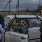 Circus labourers chat with local taxi driver